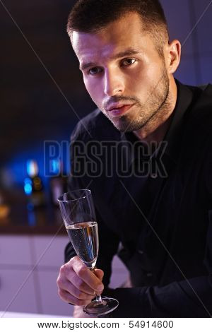 Evening portrait of young man in black shirt holding champagne flute.