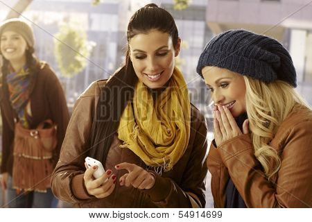 Outdoor photo of female friends looking at photos on mobilephone.