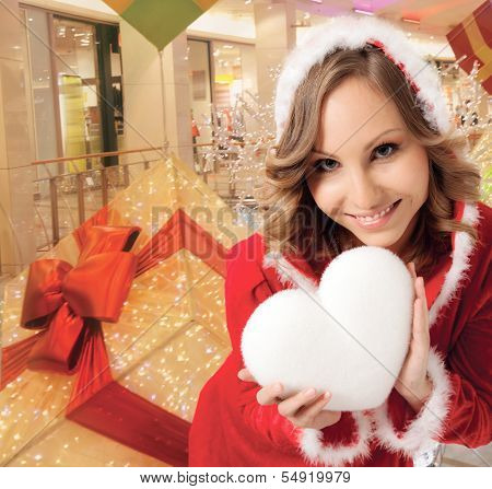 happy smiling Santa woman indoors, holding white heart, background digitally added, work path