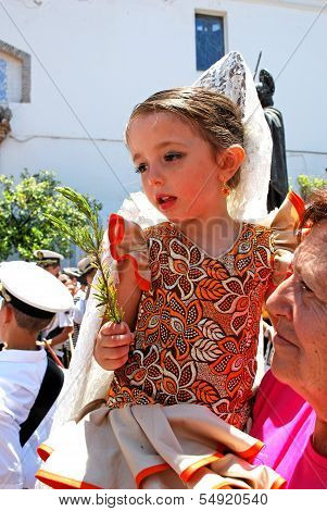 Spanish girl holding sprig of rosemary for luck, Marbella.