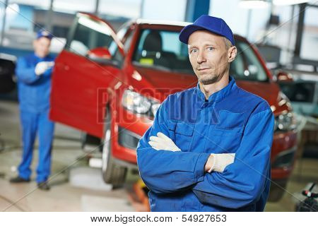 Portrait of repairman auto mechanic in front of automobile bodywork repair shop service station