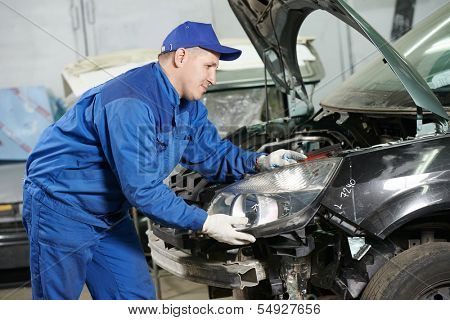 mechanic matching automobile headlight lamp to damaged car at repair service station
