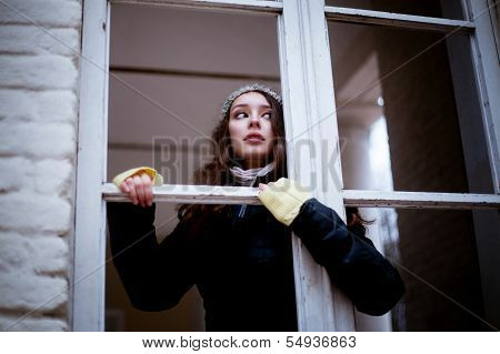 Woman looking through the window and fearing of something