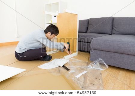 Asian man assembling table at living room