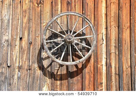 Fassade of an old Cottage with Wheel at Sunlight