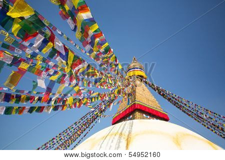 Bodhnath Stupa in Kathmandu with Buddha Eyes and prayer flags, on clear blue sky background.