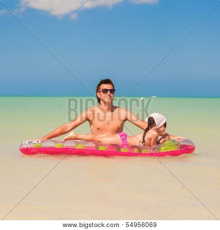 Young Father With Cute Daughter On An Air Mattress In The Sea