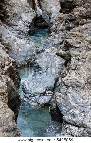 Narrow Mountain Stream Flows Among Blue Striped Rocks