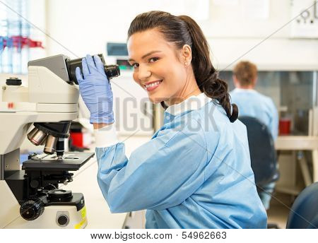 Portrait of happy female researcher using microscope in laboratory
