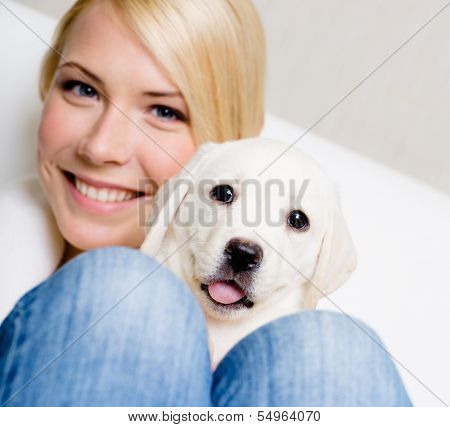 Close up of woman in white sweater with puppy sitting on her knees