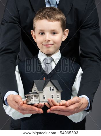Close up of little boy and somebody's hands keeping house model. Concept of real estate and business