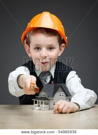 Portrait of little boy in headpiece with house model and ruler on grey background. Concept of real estate and engineering