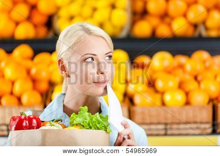 Reading list of products girl hands bag with fresh vegetables against the shelves of fruits in the shopping mall