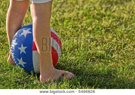 Young girl's legs and USA flag ball