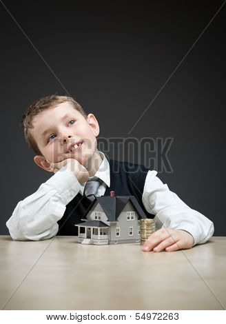 Portrait of little boy with home model and pile of coins on grey background. Concept of real estate and investment