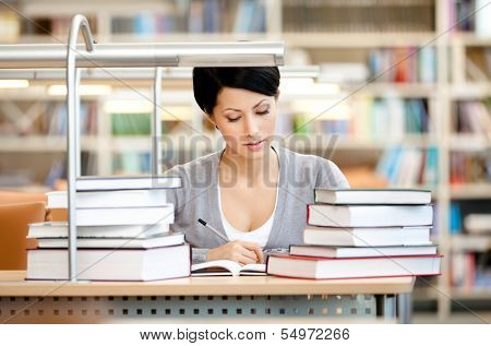Woman surrounded with piles of books reads sitting at the table at the reading hall