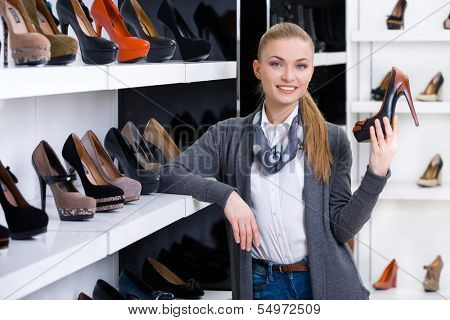 Woman with shoe in hand chooses stylish pumps looking at the shelves with numerous pumps