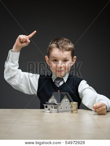 Portrait of little boy with house model and pile of coins on grey background. Concept of realty and investment