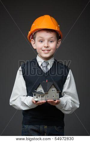 Portrait of boy in hard hat keeping house model on grey background