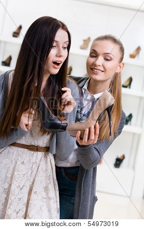 Salesperson offers shoes for the female customer in the shopping center