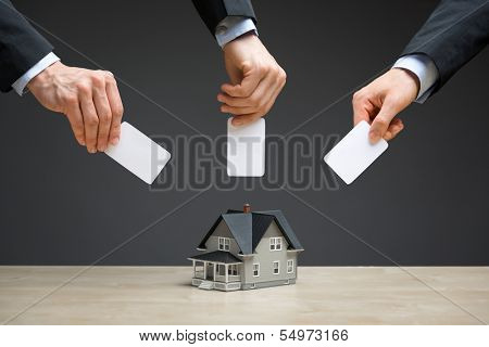 Close up of little house and hands with copyspace on grey background. Concept of real estate and investment