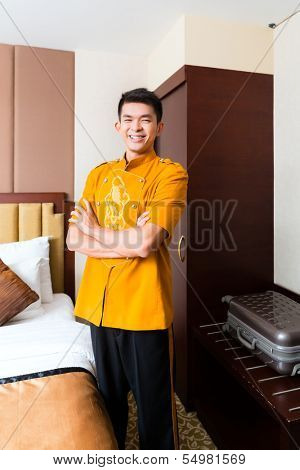 Asian Chinese baggage porter or bell boy or page bringing the suitcase of guests to the luxury hotel room