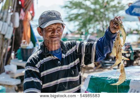 Thai fisherman showing today's catch