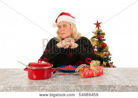 Elder woman of mature age alone with the Christmas dinner