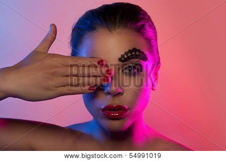 Beauty portrait of a beautiful woman covering her right eye with the hand in pink and purple lights with avant-garde makeup