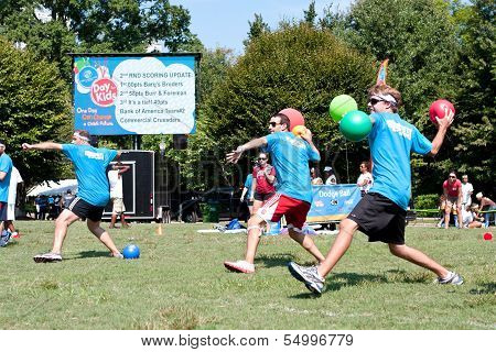 Three Men Throw In Unison At Outdoor Dodge Ball Game