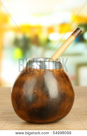 Calabash and bombilla with yerba mate on wooden table