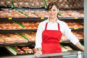 Portrait of beautiful saleswoman smiling while standing at counter in butcher's shop