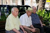 Three men sitting on a park bench, Malaga, Spain.