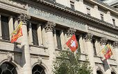 stock photo of old post office  - Close up on old post office building with Geneva and swiss flags - JPG