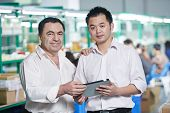 stock photo of assemblage  - caucasian businessman manager and male chinese worker man in china factory manufacturing production - JPG