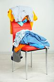 image of slut  - Heap of  clothes on color chair - JPG