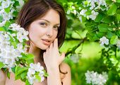 foto of nearly nude  - Portrait of young woman touches her face standing near the flowered tree in the park - JPG