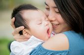 stock photo of yawn  - Happy mother kissing the cute baby yawning - JPG