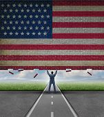 stock photo of free-trade  - Break into the American market business concept with a businessman lifting up a brick wall with the flag of the United States painted on the surface as a metaphor for access to free trade and new investment opportunity - JPG