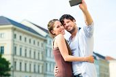 Man and woman or young couple making trip as tourists in Munich and making snapshot with the smartph