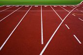 picture of 8-track  - White lines on red running track with green grass - JPG