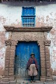 MORAY, PERU - JULY 15: woman in front of ancient door in the peruvian Andes at Moray in Cuzco Peru o