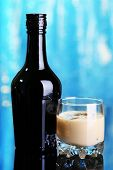 stock photo of bailey  - Baileys liqueur in bottle and glass on blue background - JPG