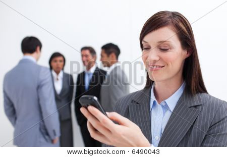 Smiling Manager Sending A Text With A Mobile Phone