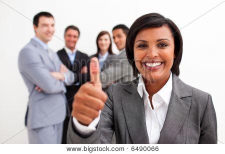 attraktive weibliche Executive Lächeln in die Kamera mit Daumen bis