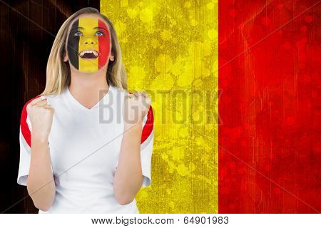 Excited belgium fan in face paint cheering against belgium flag in grunge effect