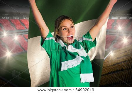 Cheering football fan in green jersey holding nigeria flag against vast football stadium with fans in yellow and red