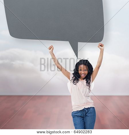 A young happy woman with speech bubble against clouds in a room