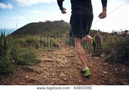 trail running athlete exercising for fitness and health outdoors on mountain pathway