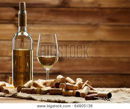 Bottle and glass of white wine on a wooden table among corks